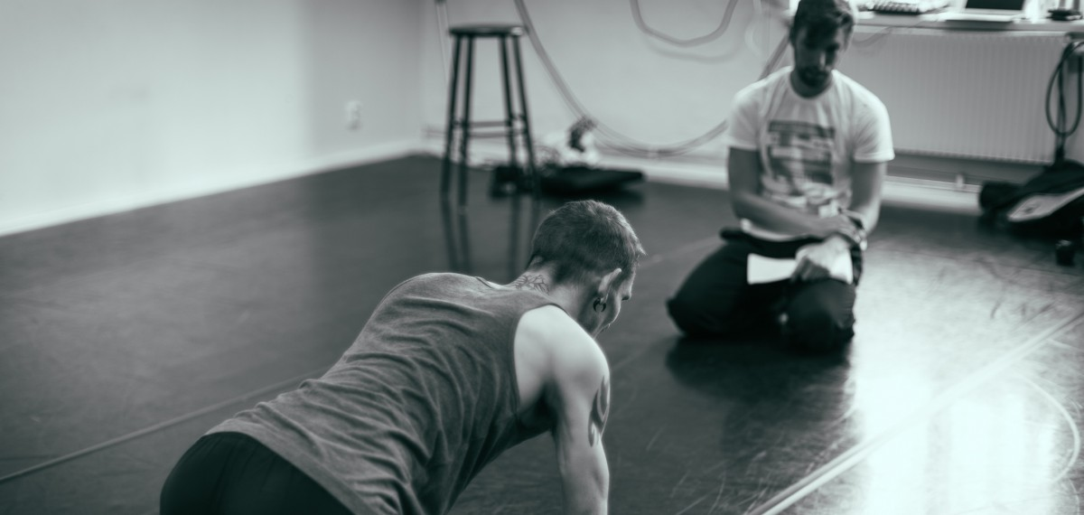 Graham Adey in rehersal with Dan Daw. Sitting casually in the studio, choreographers notes in hand, closely observing Dan's movement.