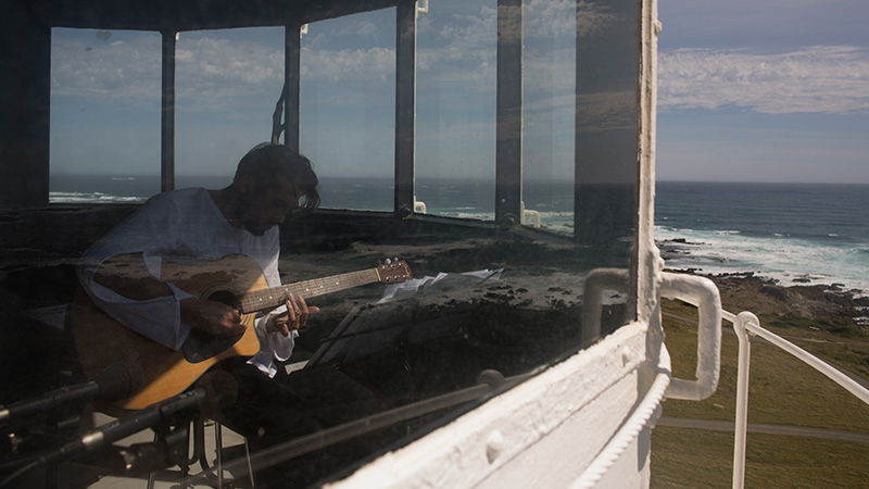 Ekrem Mulayim playing an acoustic guitar in a lighthouse. Coastline and ocean off in the background. Photo taken from outside, looking in.