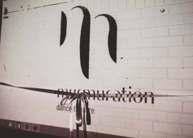 Projection of Murmuration Dance Theatre logo onto a white brick wall, ribbon tied in a bow across the logo.