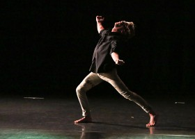 Male dancer on stage. Lunging forward, arms open wide, head facing up towards ceiling.
