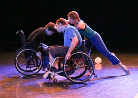 Two performers in wheelchairs side by side, facing each other. Another performer reaching towards them.