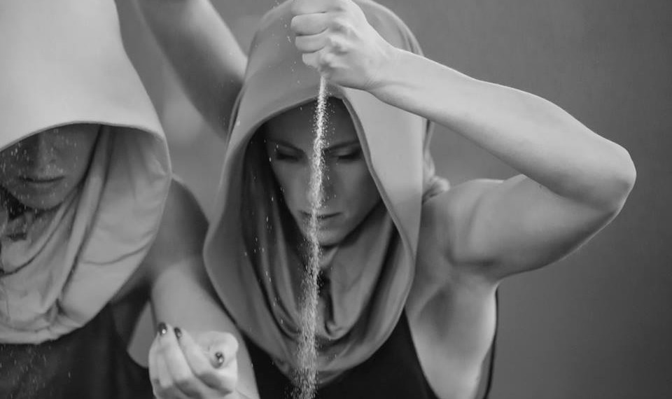 Brianna Kell in performance. Hood like head dress covering hair and neck, arm above head, sand streaming out of her closed fist towards the floor.