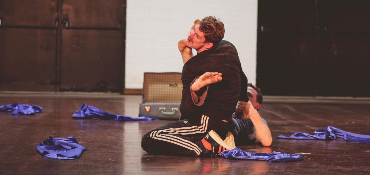 Bowerbirds-sharing.-Daniel-Dan-wrestling-Daniels-foot-on-Dans-face-sense-of-motion-surrounded-by-scraps-of-blue-fabric-and-an-open-suitcase