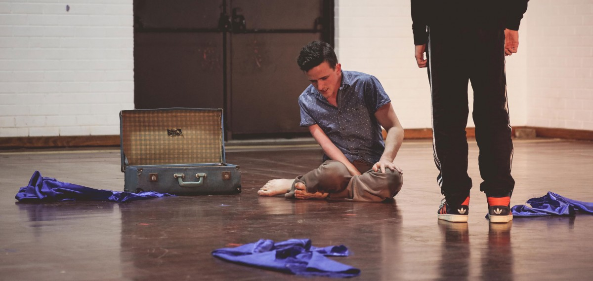 Bowerbirds-sharing.-Daniel-sitting-next-to-an-open-empty-suitcase-surrounded-by-scraps-of-blue-fabric-Dan-standing-over-him.-jpg
