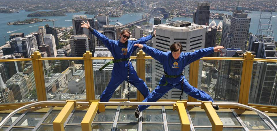 Christopher Bunton on the top of a building in Sydney, doing a star jump. Sydney Opera House & the Harbour Bridge can be seen in the distance.