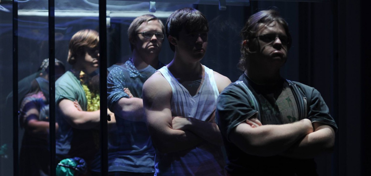 Christopher Bunton in performance, standing in a line with 3 other male performers. All have arms crossed, looking straight ahead.