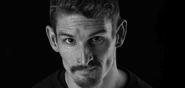 Close up of Dan Daw's face against a black background. He's looking straight towards the camera, no expression. Black & white.