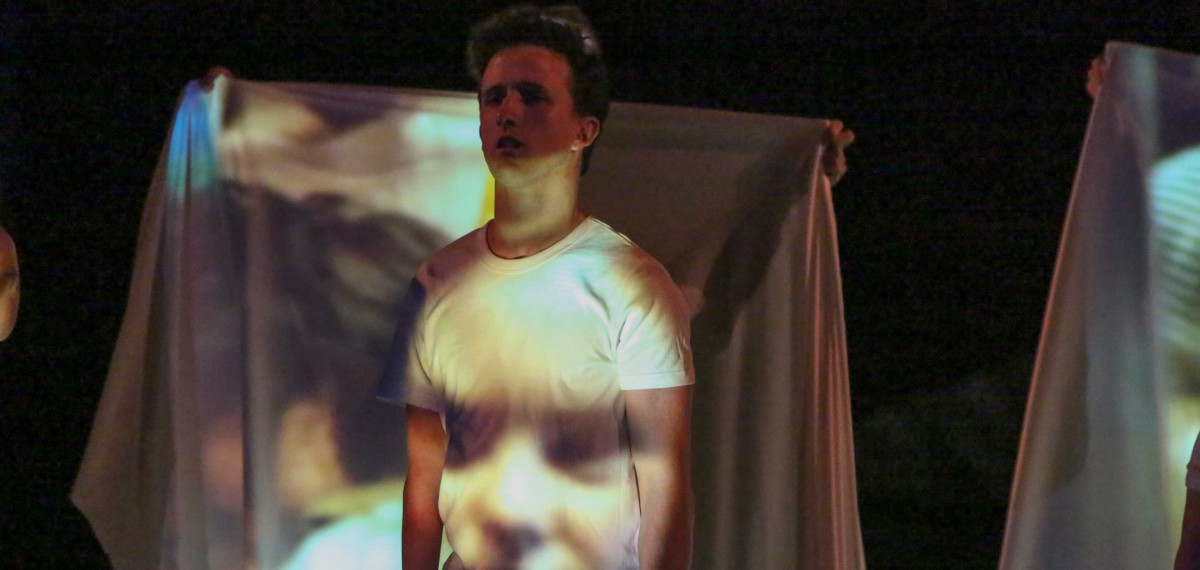 Daniel Monks in performance. Standing, looking directly ahead. Image of a face projected onto his white shirt & white sheets behind.