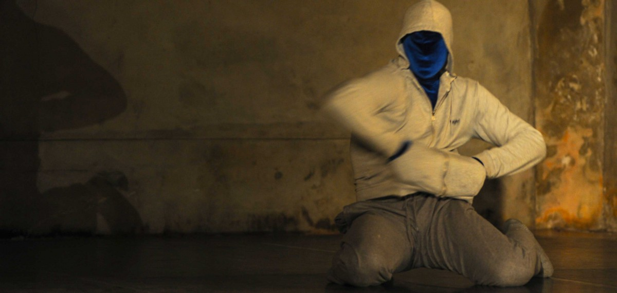 Dean Walsh in performance. Face covered with a form fitting blue fabric, wearing a white hooded jumper. His shadow cast on the background.