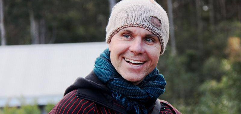 Close up of Dean Walsh, dressed in beanie and scarf, not looking at the camera, smiling.