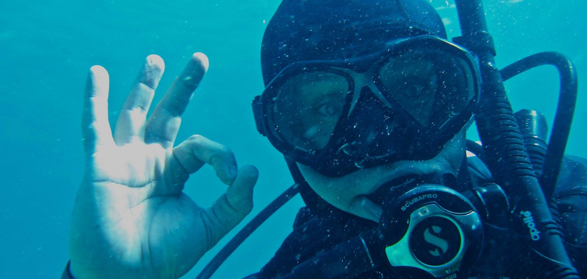 Dean Walsh scuba diving. Close up of his face in the scuba mask, hand making the OK symbol.
