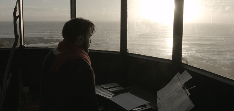 Ekrem Mulayim at a keyboard, sheets of music front of him. Looking out the windows of a lighthouse at the horizon, sun setting on the ocean.