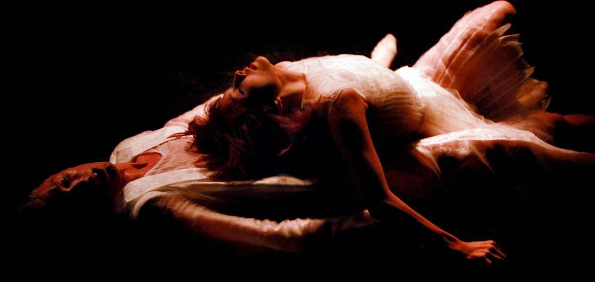 Graham Adey in performance. Black background, all dressed in white. Lying down, female performer lying on him, her back on his stomach.