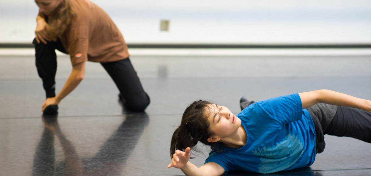 Hazuki Kojima in the studio. Lying on the floor, looks as if she is midway through rolling over. Another dancer crouching in the background.