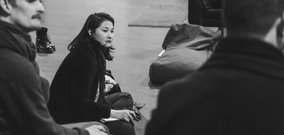 Hazuki-sitting-on-the-floor-pen-and-notebook-in-hand-looking-thoughtful-as-she-listens-to-someone-out-of-shot-speaking.-Black-white