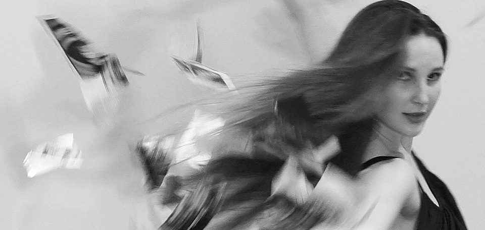 Imogen Cranna in performance. Long hair and arms a blur with motion. Multiple photos also floating through the air. Black & white.