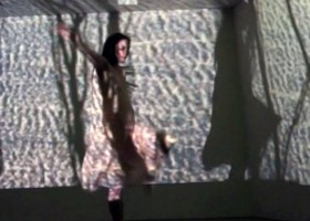 Imogen Cranna in performance, wearing a white dress, a large textured projection covers her and the whole stage, like the ocean.