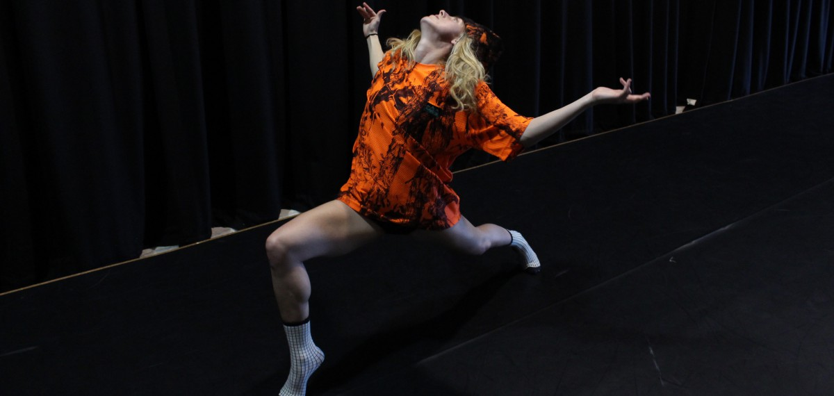 Brianna Kell in performance, wearing a bright orange shirt & white socks. Lunging forward, arms out to the sides, elbows bent, head tilted back.