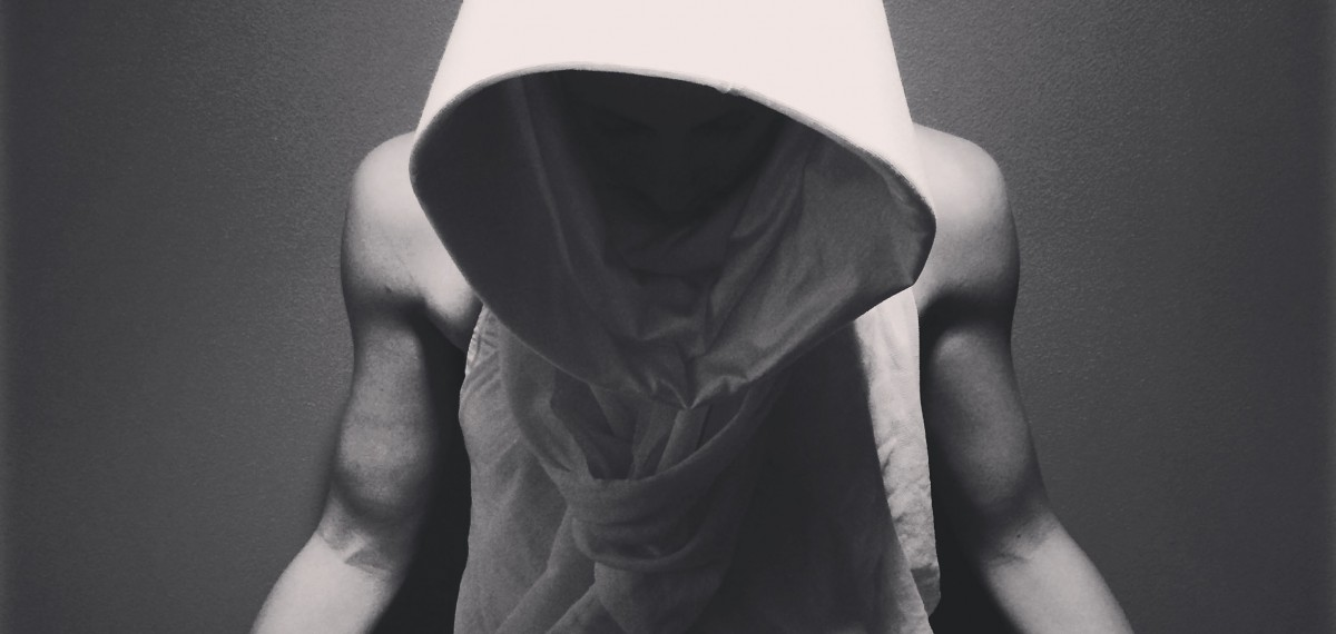 Brianna Kell. Standing, arms by sides, looking down. Head covered by a large hood, casting shadow on her face. Black and white.