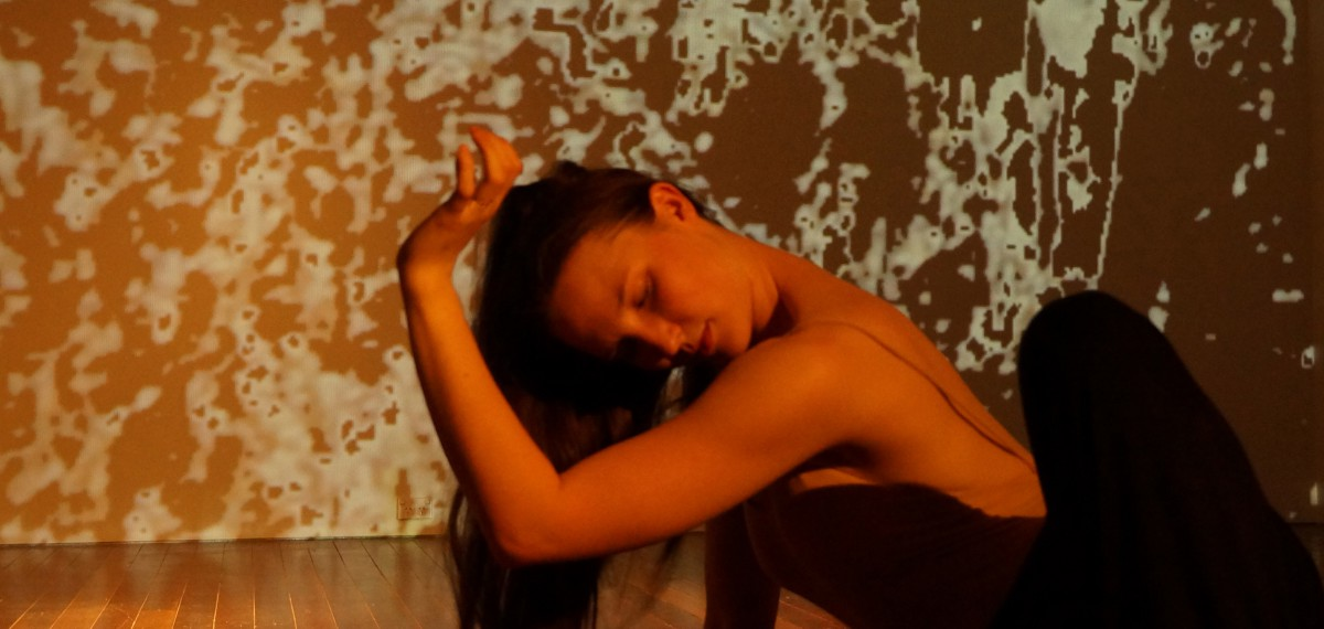 Imogen Cranna in performance. Sitting on stage, warm lighting and projected patterns on wall behind her. Arm angled, framing face.
