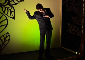 Matthew Massaria in performance. Standing the corner of a room, wall behind him lit with green lights & painted with the outline of 4 large black leaves.