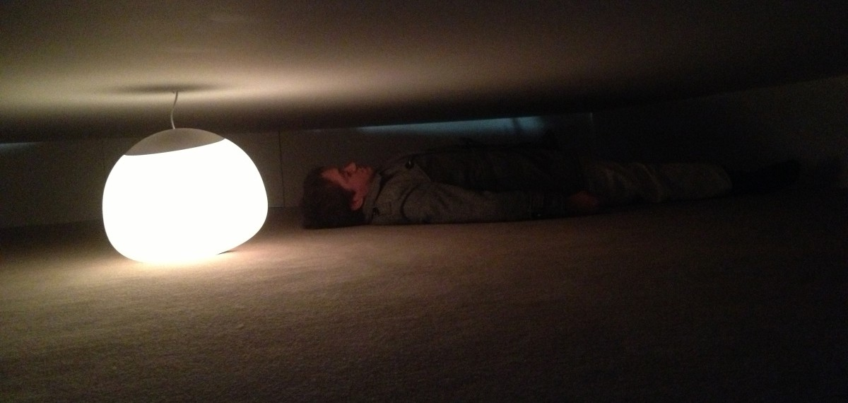 Matthew Shilcock lying in a narrow horizontal space, between two walls, large bright circular light providing the only light. Large shadows.