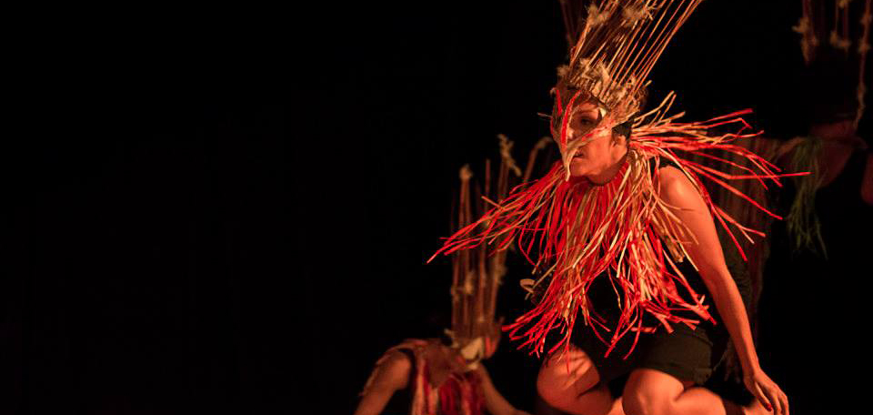 Melinda Tyquin in performance. Appears to be jumping, and dressed in an elaborate Aboriginal/Islander style headdress & costume.