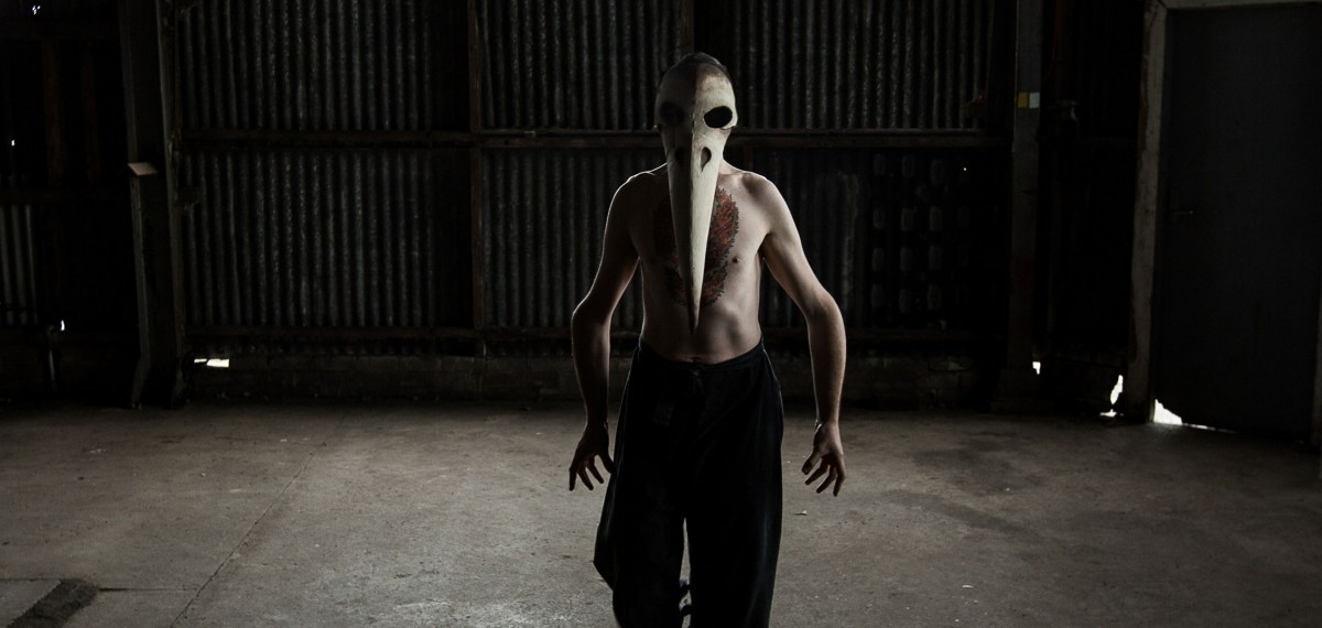 Matt-standing-facing-the-camera-in-a-dark-shadowy-space.-Wearing-a-bird-like-mask-with-a-long-beak-no-shirt-and-black-pants.