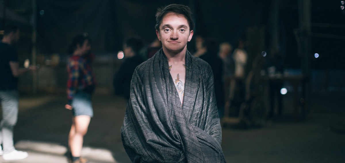 Matt-standing-facing-the-camera-wearing-a-grey-dressing-gown-smiling-subtly-hands-in-pockets.