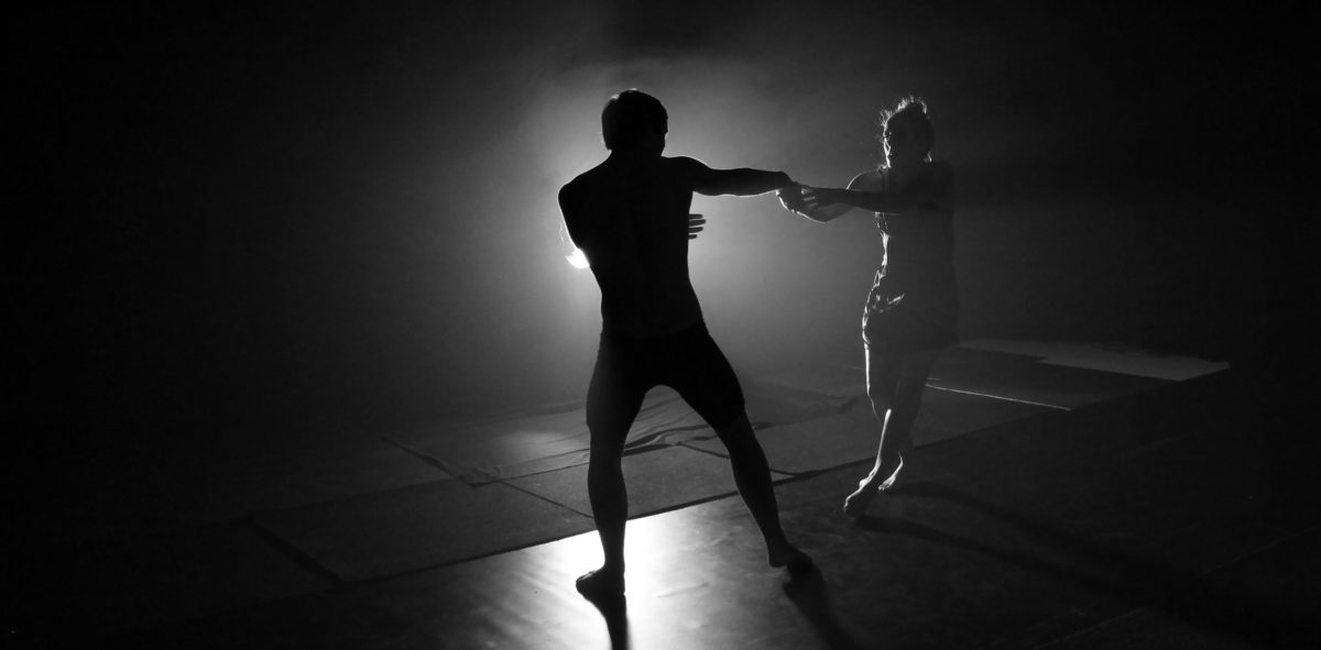Black and white image of silhouetted full body male and female dancers holding each others hand in full extension against white light.