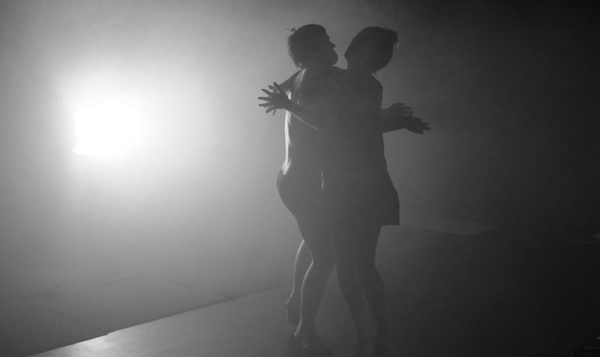 Black and white image of male and female silhouetted dancers holding each other in a full body standing hug.