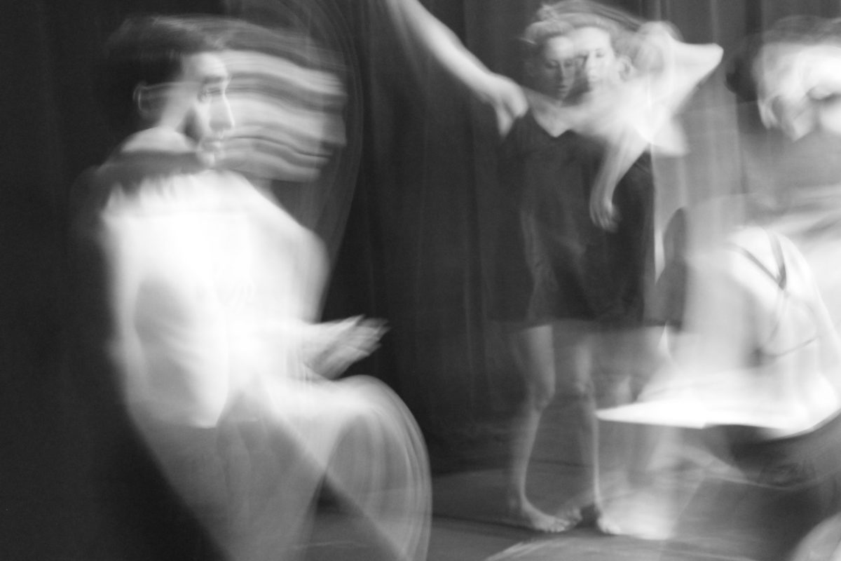 Blurred black and white image of three performers moving around against a black curtain.