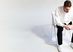 On-One-Condition-promotional-image,-Dan-wearing-white-shirt-and-shoes-with-black-pants,-sitting-on-a-white-chair,-white-background