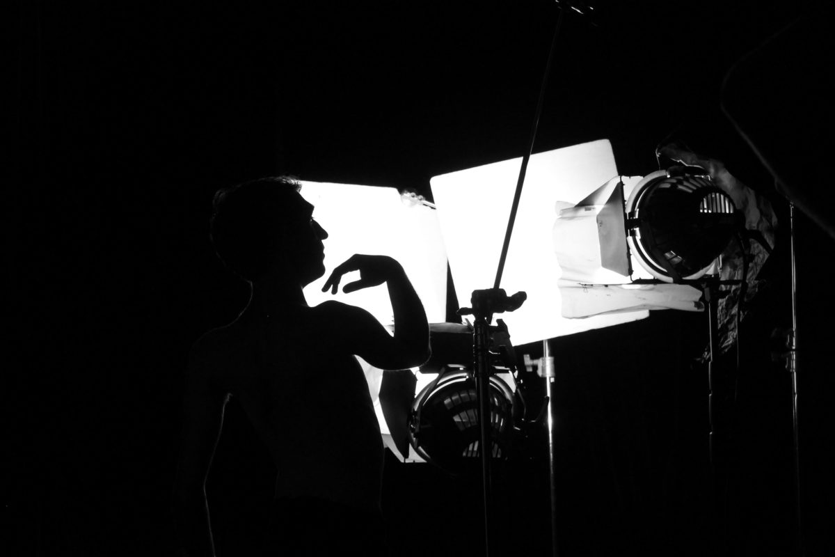 Black and white image of silhouetted mans top half body against strong white light in background.