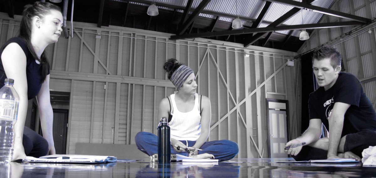 Sarah-Vyne in the studio with two artists during a creative development. 3 of them sitting down with notebooks and drink bottles, engaged in dSarah-Vyne in the studio with two artists during a creative development. 3 of them sitting down with notebooks, engaged in discussion.iscussion.