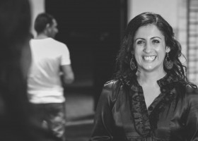 Sarah-Vyne-Vassallo-smiling-eagerly-as-she-is-being-interviewed-by-Ausdance-NSW-at-the-Murmuration-company-launch-hair-out-wearing-a-black-silky-top.-Black-white