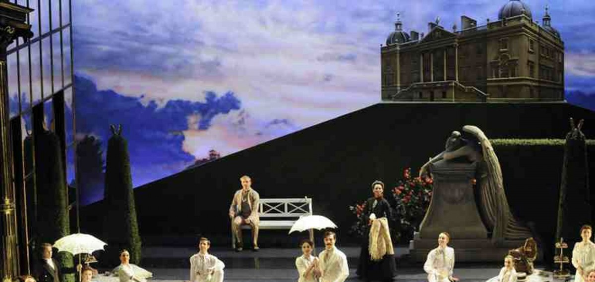 Stephen-Metcalf-set-design-seen-in-performance.-Stately-home-in-the-background-deep-blue-cloudy-sky-tall-green-trees-all-performers-in-white