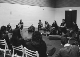 The-Flock-a-gathering-of-Murmuration-artists-and-community-members-sitting-on-bean-bags-and-chairs-in-a-rough-circle-in-discussion.-Black-and-white