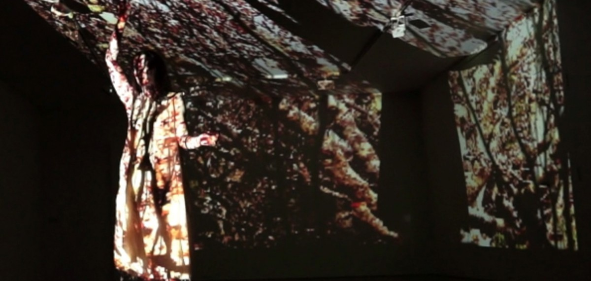 Imogen Cranna in performance. Wearing a white dress, a large projection of a forest covers her and the stage.