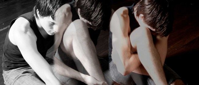 3 images of a male dancer layered into one image that changes from colour to black and white. Dancer sitting on the floor, head looking down.