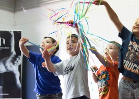 A-group-of-four-young-boys-participating-in-Mini-Murmurs-class-dancing-with-ribbon-sticks