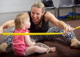 A-mother-and-child-sitting-on-the-floor-in-a-Mini-Murmurs-class.-Mother-smiling-at-the-child-while-stretching-a-large-yellow-elastic-around-her
