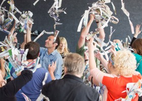 Workshop at Museum of Contemporary Art. A large group of teachers throwing torn up strips of newspaper into the air, making it appear like a snow storm.