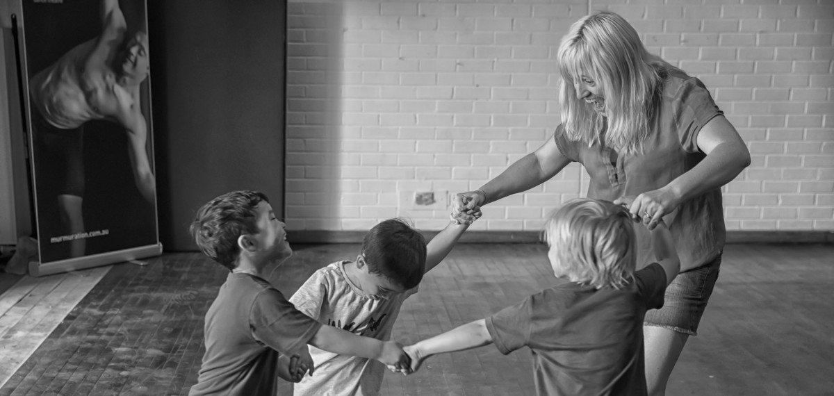 3 young boys & a mum in a Mini Murmurs class, holding hands in a circle, faces excited. Murmuration banner in the background, black & white
