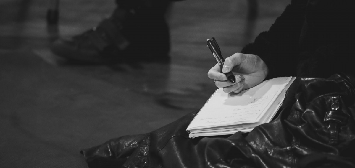 A-close-up-shot-of-someone-writing-on-a-notebook-with-a-pen-at-the-artists-forum.-Black-and-white
