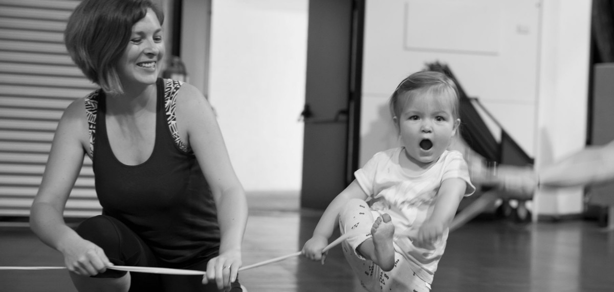 A mother watches her toddler smiling as the girl dances with a large stretchy elastic in a mini murmurs class. Black and white