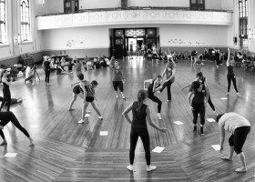 A wide shot of a large hall, students spread around the room all in different positions doing different tasks, room brightly lit sun through large windows. Black&white