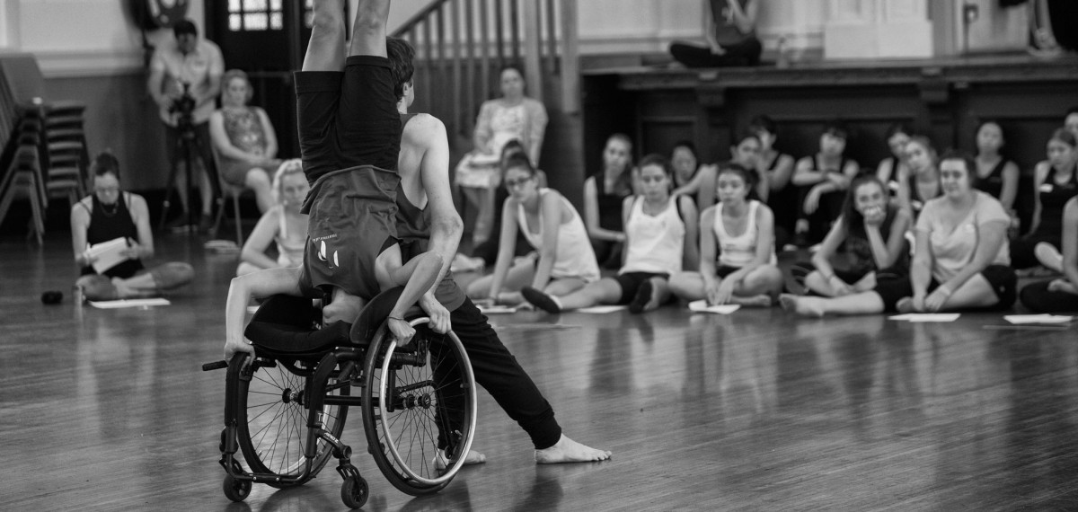 Large group of students, sitting on the floor watching Days Like These sharing, Mel doing a head stand on Matt's wheelchair while he sits in front. Black&white
