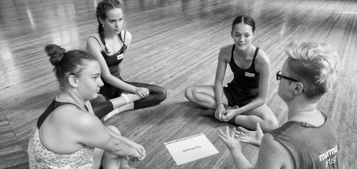 Murmur Artist Karen sitting with 3 students, deep in coversation, and piece of paper in front of them that says 'confusion'. Black and white