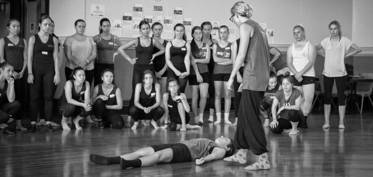 Murmur artists deomnstrating a rolling task in front of a large group of students standing and watching intently. Black and white
